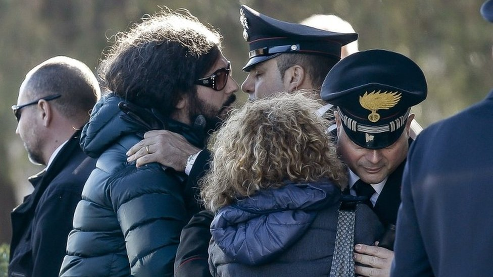 "Giovanna Di Agostino, mother of Italian victim Fabrizia Di Lorenzo, and her son Gerardo, left, are hugged by authorities upon their arrival from Berlin with the coffin of her daughter Italian victim Fabrizia Di Lorenzo, at Rome""s military airport of Ciampino, Saturday, Dec. 24, 2016"