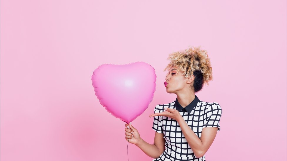 Woman holds pink heart-shaped balloon