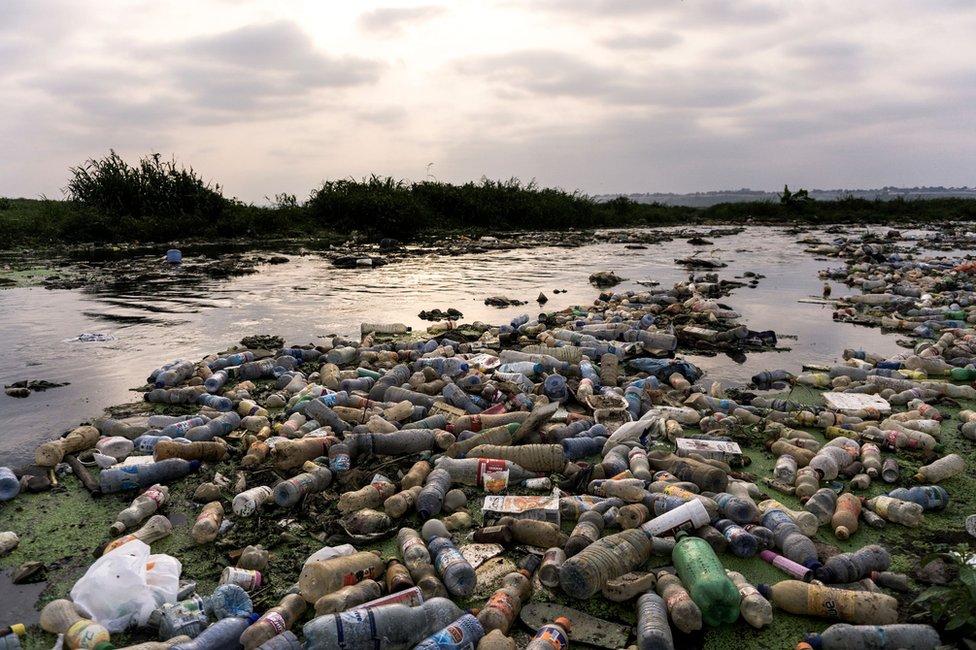 Botellas contaminando un río.