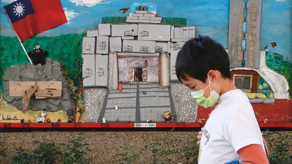 A kid wearing a mask walks past a mural with a national flag of Taiwan amidst a recent cluster of domestic transmissions of Covid-19 ahead of the Lunar New Year.