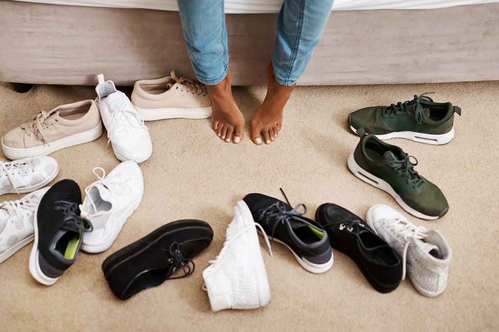 Pies de mujer rodeados de zapatillas.