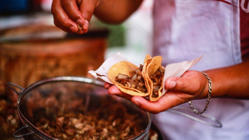 Persona cocina tacos