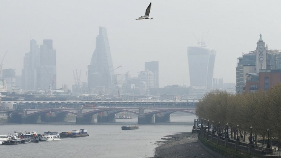 A seagull flies through smog above the skyline of the City of London on April 2, 2014.