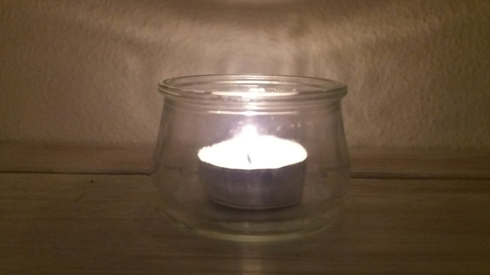 A tea light in a glass candle holder shines brightly on the 80th anniversary of Kristallnacht