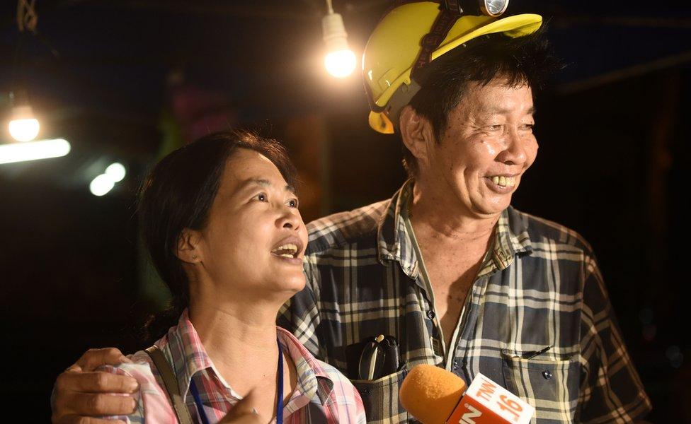 Familiares de los niños atrapados en una cueva en Tailandia celebran a la entrada de la misma.