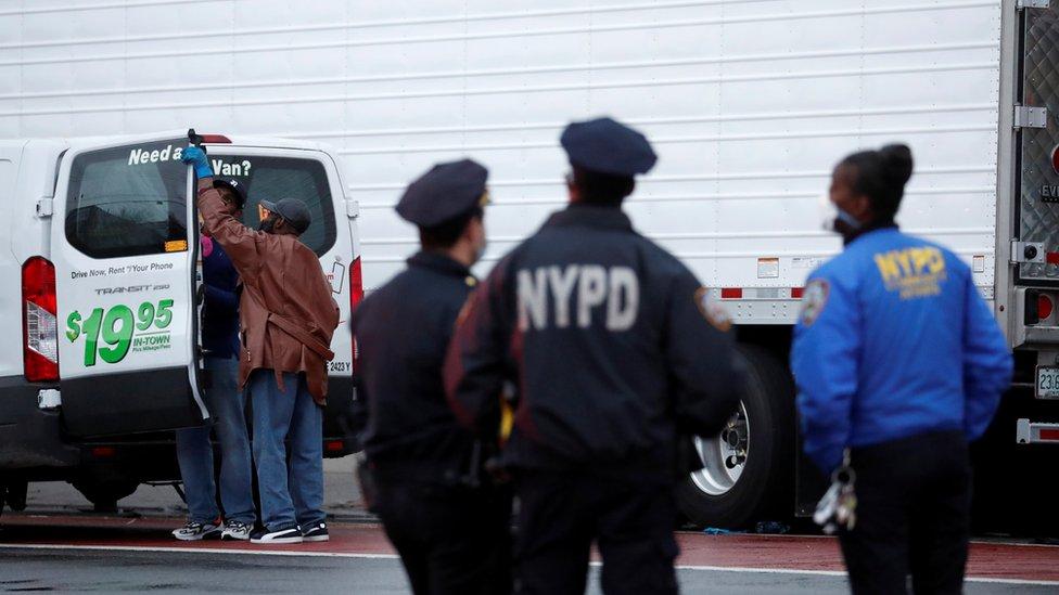 Policía al lado de los camiones llenos de cadáveres en Nueva York.