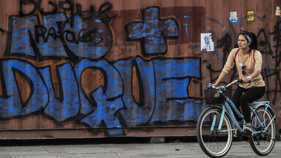A woman rides her bike by a graffiti against Colombian President Ivan Duque, in Bogota on November 24, 2019.