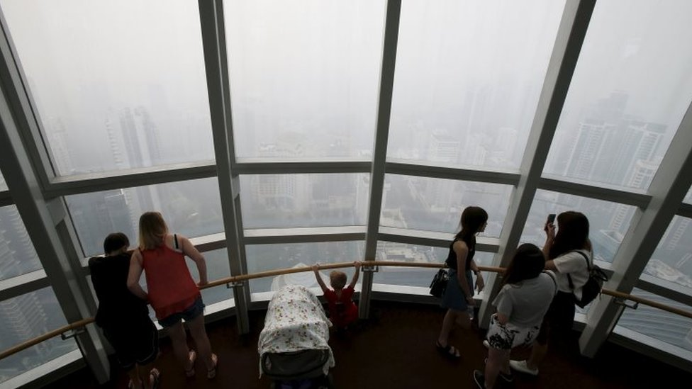 People look from an observation room at the haze-shrouded shopping district of Orchard Road in Singapore September 24, 2015.