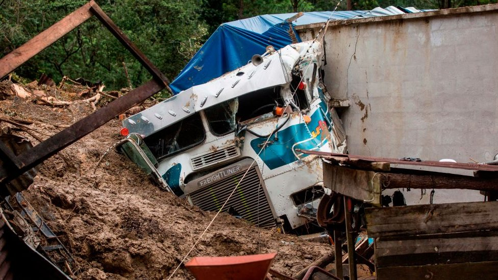 Truck covered by mud beside a building in Queja, Guatemala, on 7 November 2020