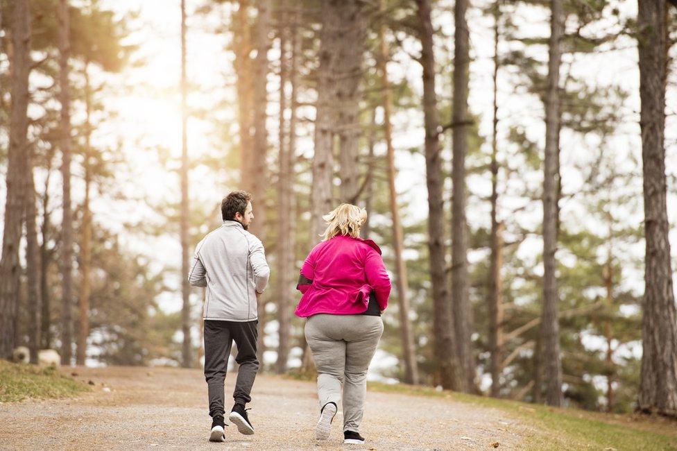 Mujer obesa y hombre delgado corriendo.