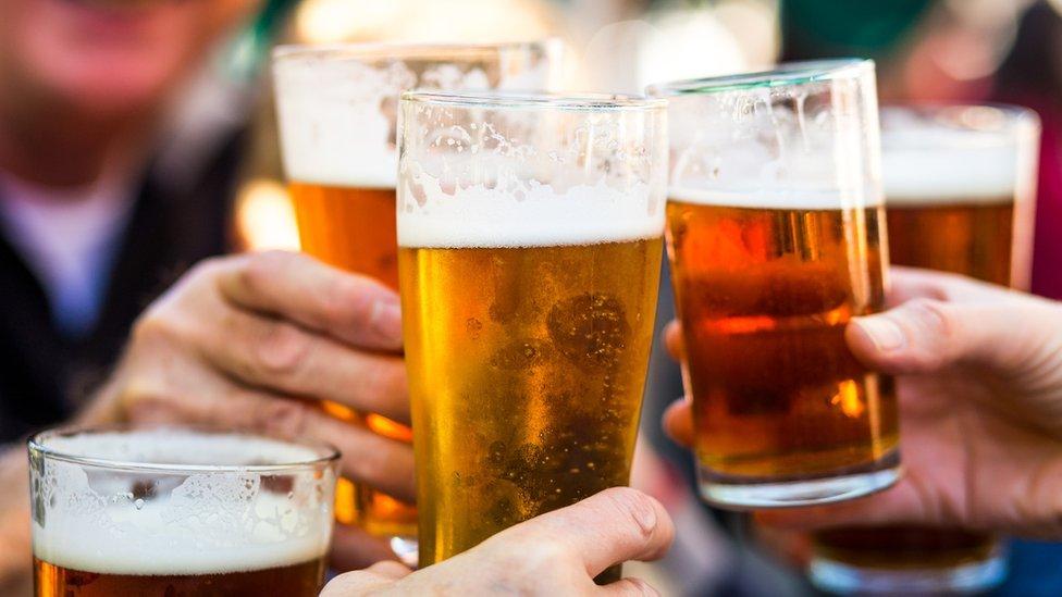 Personas brindando con cerveza.