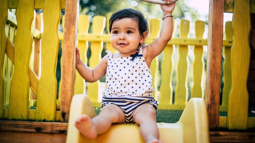 Una bebé jugando en una resbaladera.
