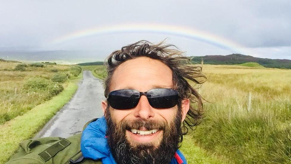 Chris with a rainbow behind him