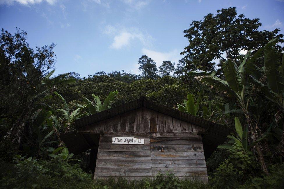 Casa con cartel con el nombre de la aldea en Xeputul II, Guatemala