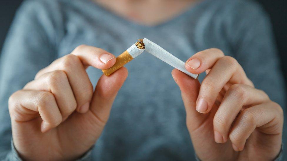 Una mujer rompiendo un cigarrillo
