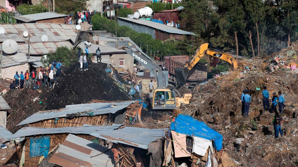Excavators move earth as rescuers work at the site of a landslide at the main landfill of Addis Ababa on the outskirts of the city on March 12, 2017