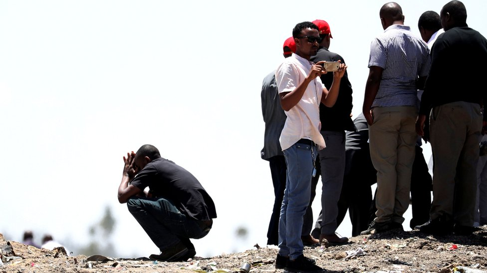 United Nations workers mourn their colleagues during a commemoration ceremony for the victims at the scene of the Ethiopian Airlines Flight 302 plane crash, near Addis Ababa, Ethiopia