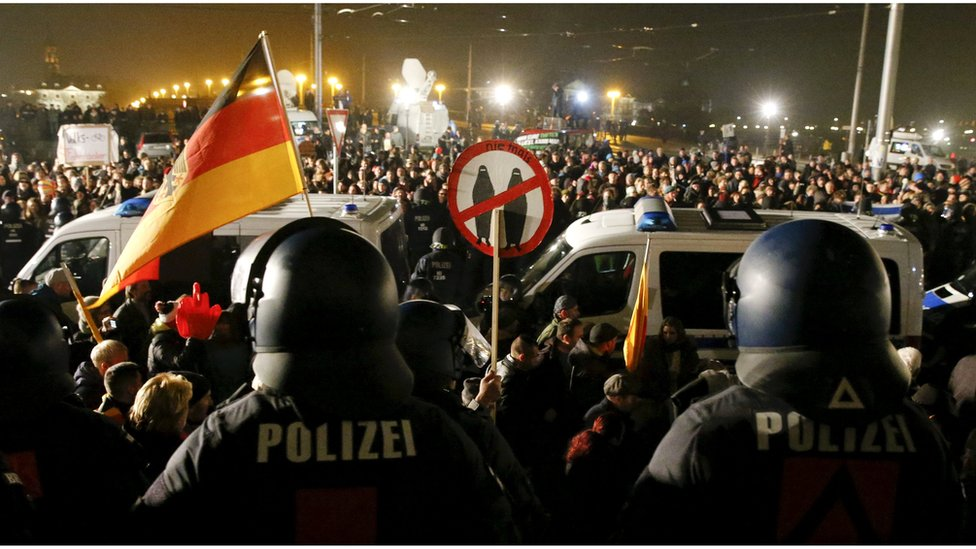 People attending an anti-immigration demonstration organised by rightwing movement Patriotic Europeans Against the Islamisation of the West (PEGIDA) walk past opponents of PEGIDA behind police cars, in Dresden, Germany October 19, 2015