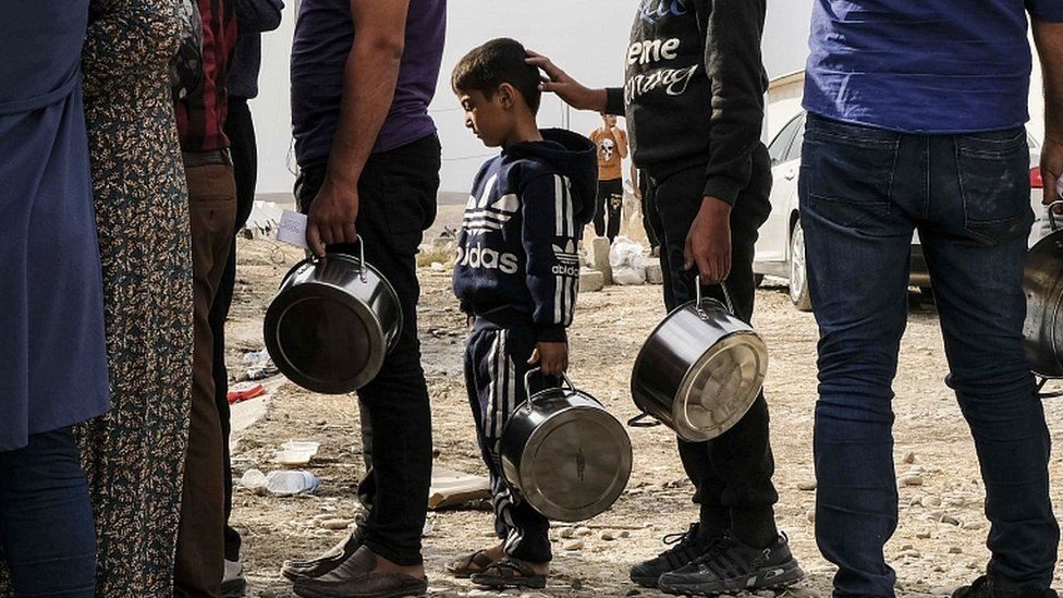 Syrian refugees fleeing the Turkish incursion in Northern Syria wait to receive water, bread and soup at the Bardarash IDP camp on October 17, 2019 in Dohuk, Iraq