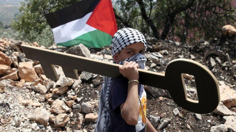 Dečak drži simbolični ključ grada Kfar Kadum, maj 2018.