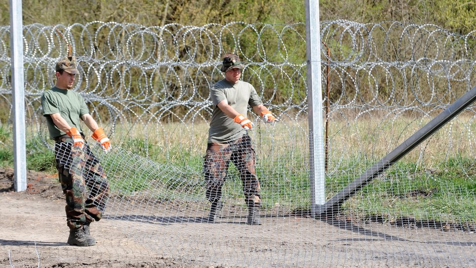 Hungarian soldiers roll out barbed wire