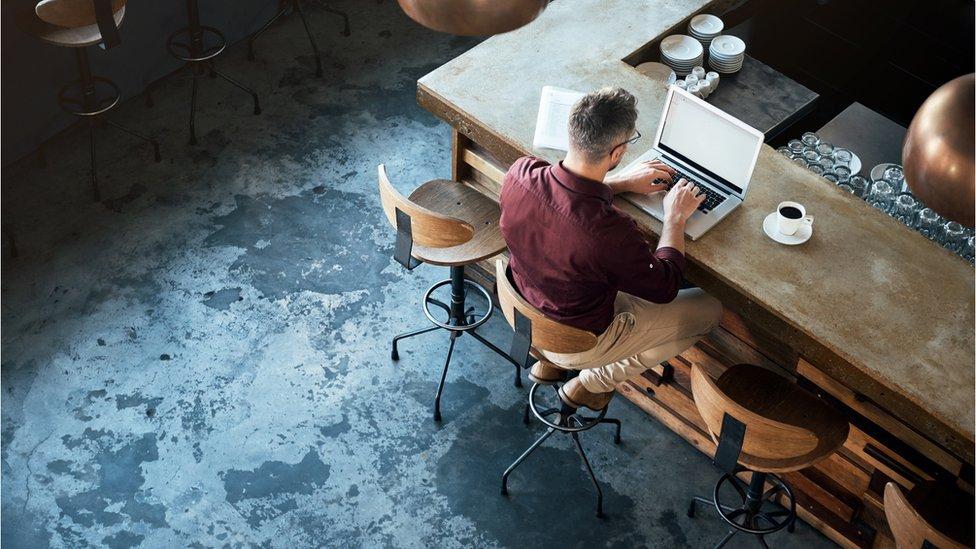 Hombre con computadora en un café