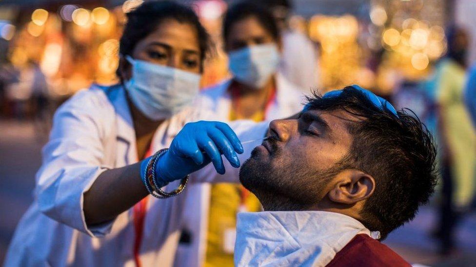 Profissional de saúde recolhe amostra de paciente para exame de covid