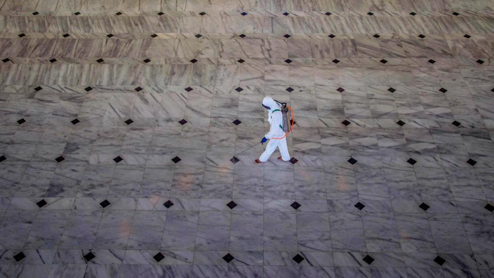 Seorang petugas kesehatan mengenakan alat pelindung diri menyemprotkan disinfektan pada lantai sebuah gedung.
