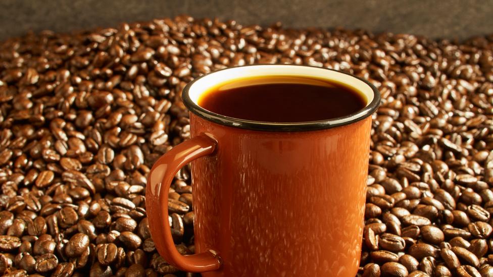 Taza de café junto a granos de café