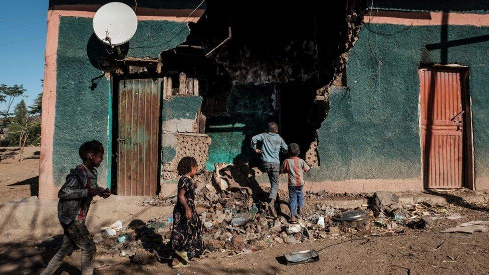 Niños juegan frente a una casa que resultó dañada durante los enfrentamientos que estallaron en la región de Tigray en Etiopía, en la aldea de Bisober, el 9 de diciembre de 2020.