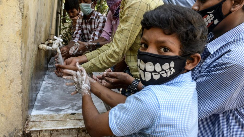 Un niño se lava las manos en India.