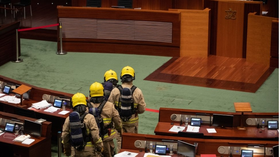 Firefighters wearing gas masks check the main chamber of the Legislative Council in Hong Kong, China, 28 May 2020