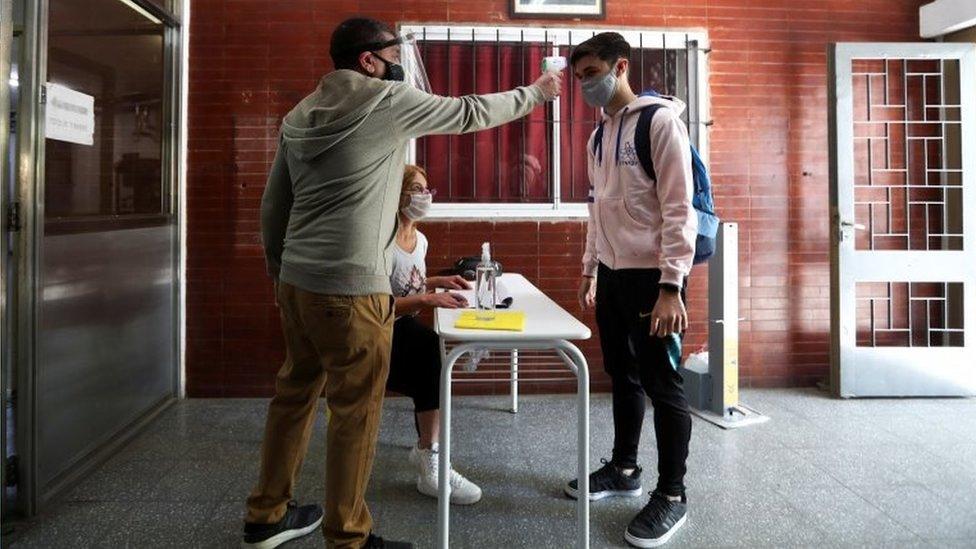 Aluno tem sua temperatura medida ao entar em escola em Buenos Aires