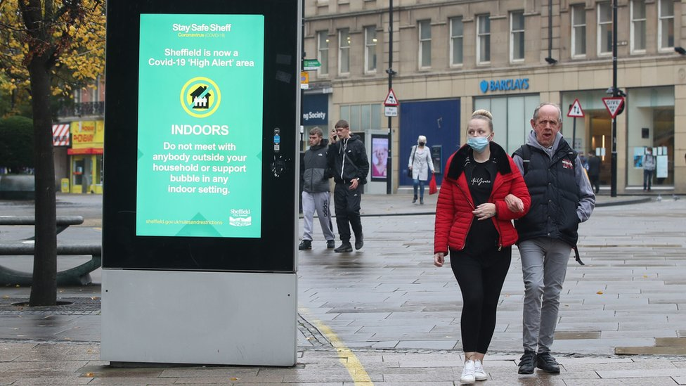 A woman wearing a face mask passes a coronavirus advice sign in Sheffield