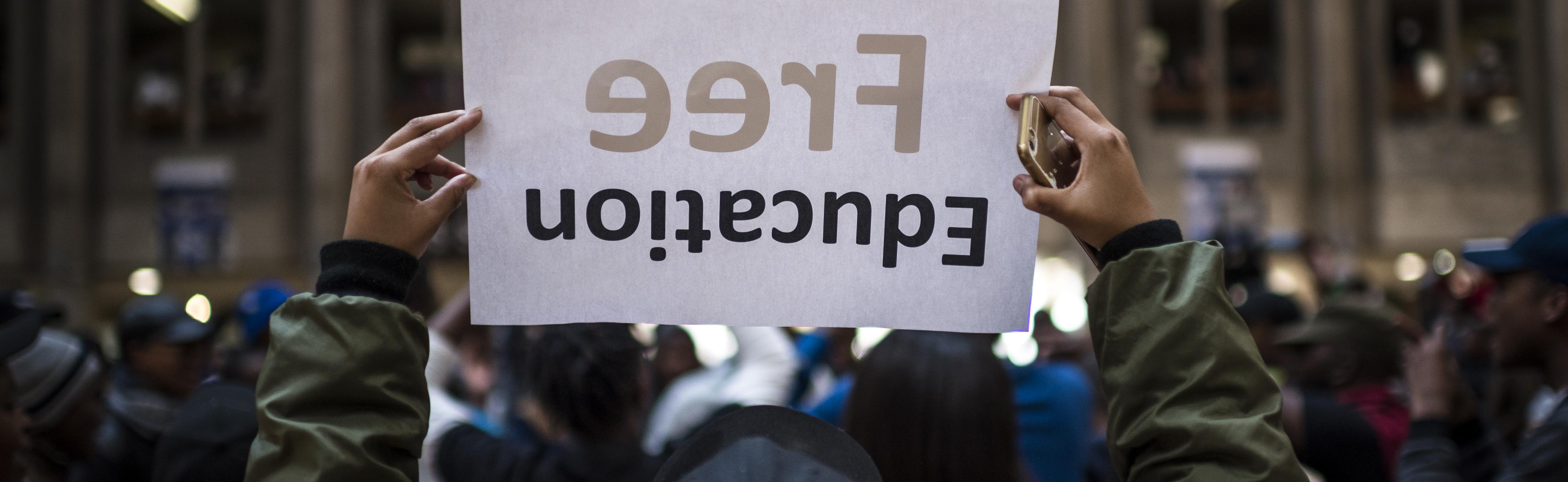 A student holds a free education poster during protest over tuition fees