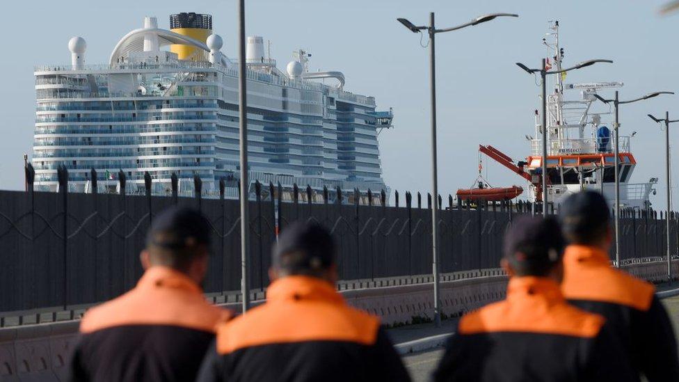 Miembros de la guarda costera italiana marchan frente al Costa Smeralda