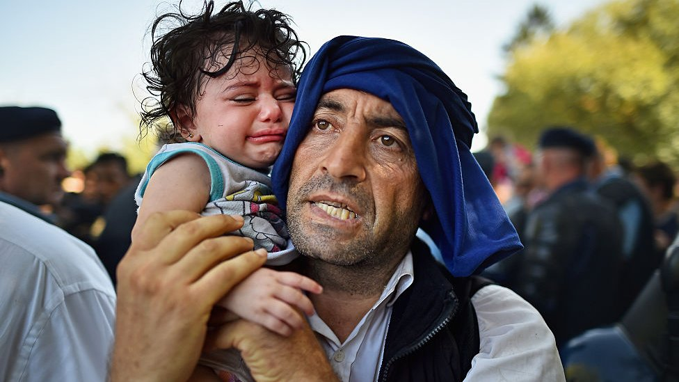 A man holds his crying child close to him as migrants force their way through police lines at Tovarnik station for a train to take them to Zagreb on September 17, 2015 in Tovarnik, Croatia.