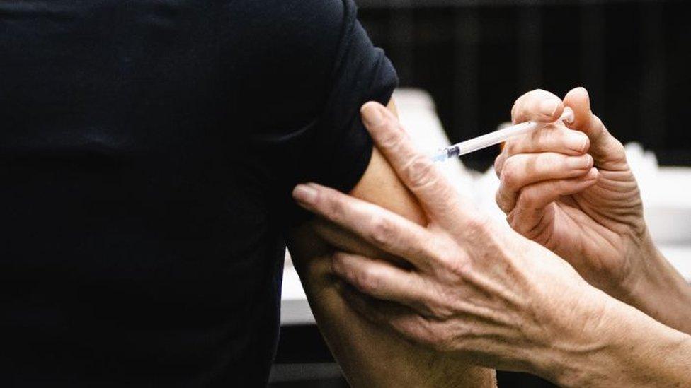 Las manos de una enfermera inyectando el brazo de una paciente