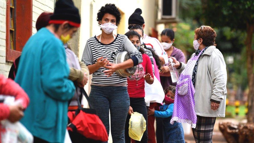Desempleados en Paraguay haciendo fila por comida.