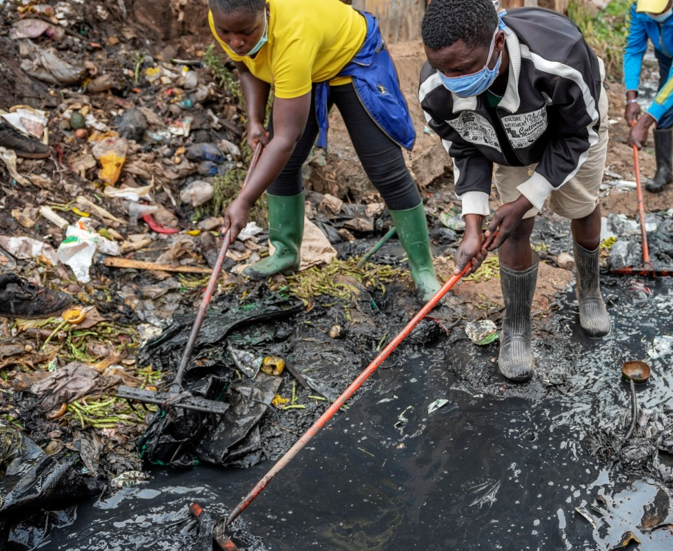 Jack Omonoi (in black jacket) working cleaning a sewer in Nairobi, Kenya