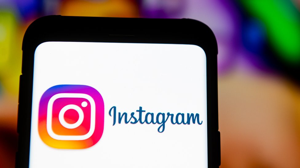 The Instagram logo is seen on a mobile phone screen in front of a vivid, but blurred
