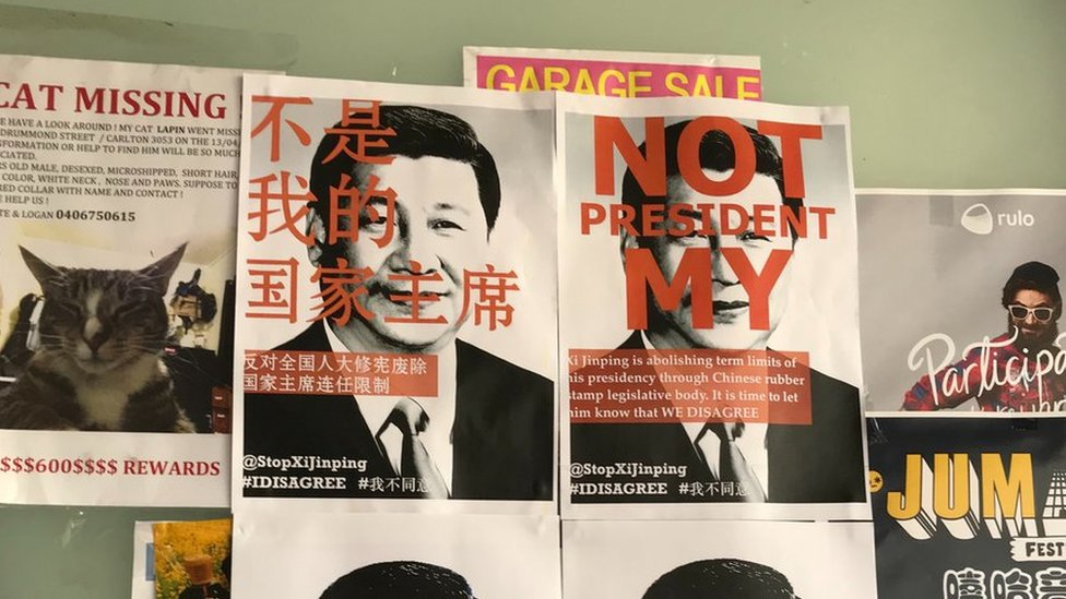 """Posters reading """"not my president"""" in Chinese and English over a photo of Xi Jinping at Melbourne University in Australia"""