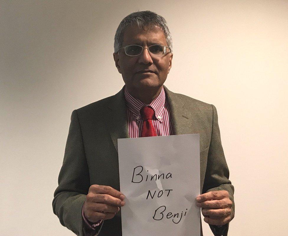 """Binna Kandola holding up a sign saying """"Binna NOT Benji"""""""