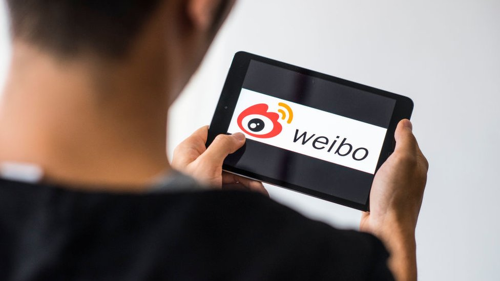 Un hombre sostiene una tableta con el logo de Weibo.