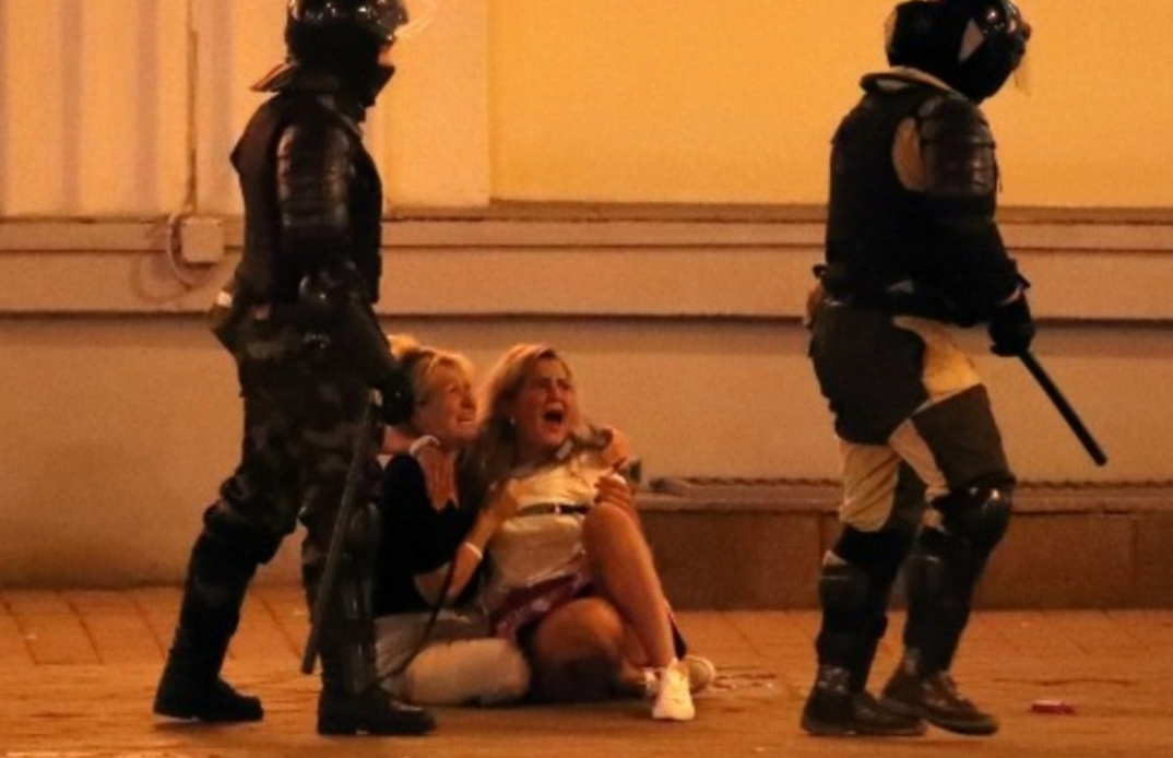 Two women on the floor, screaming, while two policemen with batons stand next to them