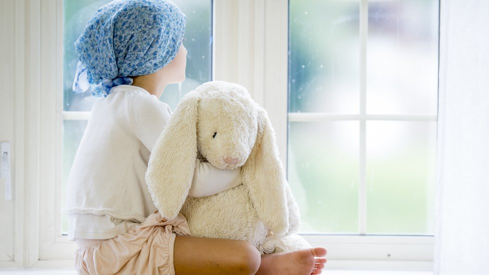 A girl with cancer sitting in a window