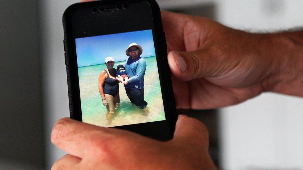 Foto a la foto de un celular con familias víctimas del colapso de un edificio en Miami.