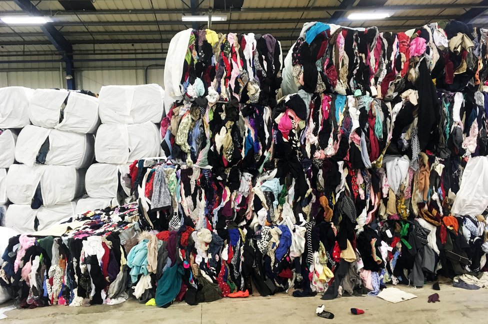 Bales of clothes at Oxfam recycling centre