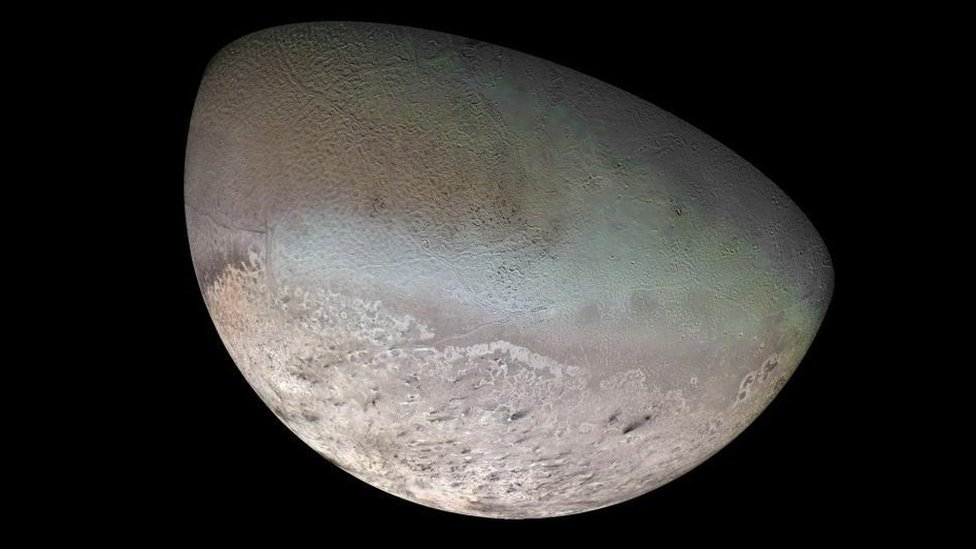 La mitad de la superficie de Tritón, Half the face of Triton, its blue-green surface is mottled like a cantaloupe