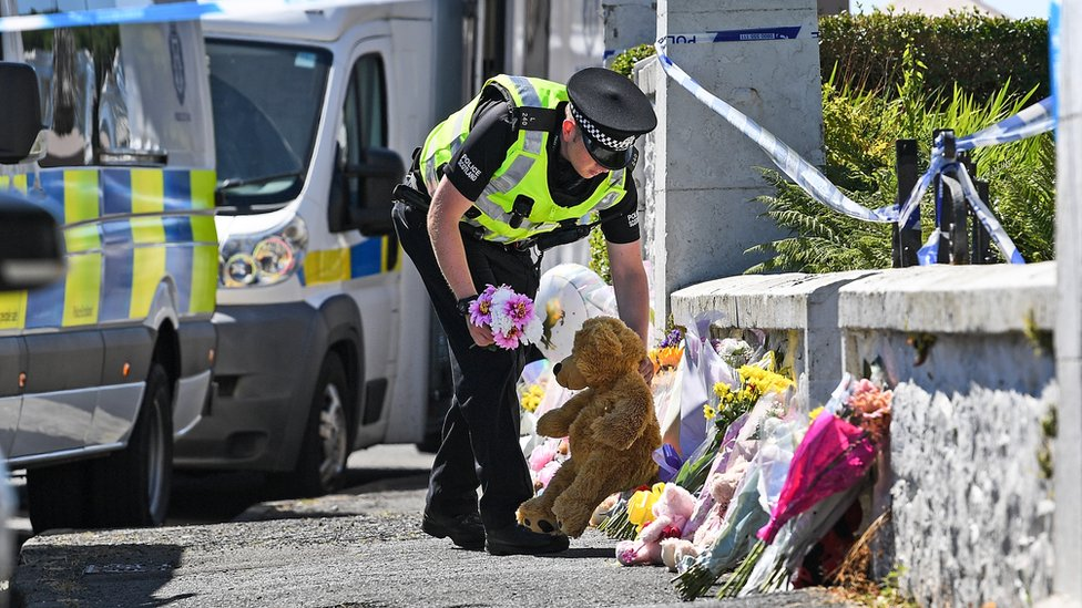 Police officer with floral tributes